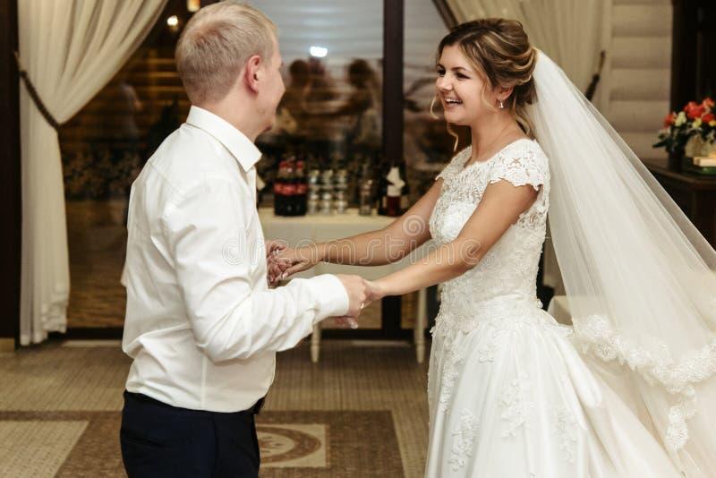 Glückliche herrliche Braut und stilvolles Bräutigamtanzen im reichen restauran lizenzfreie stockbilder
