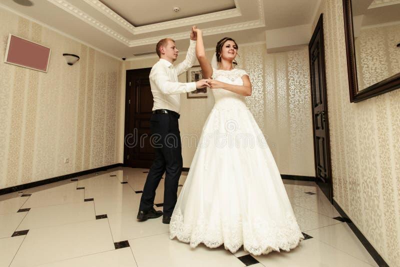 Glückliche herrliche Braut und stilvolles Bräutigamtanzen im reichen restauran stockfotografie