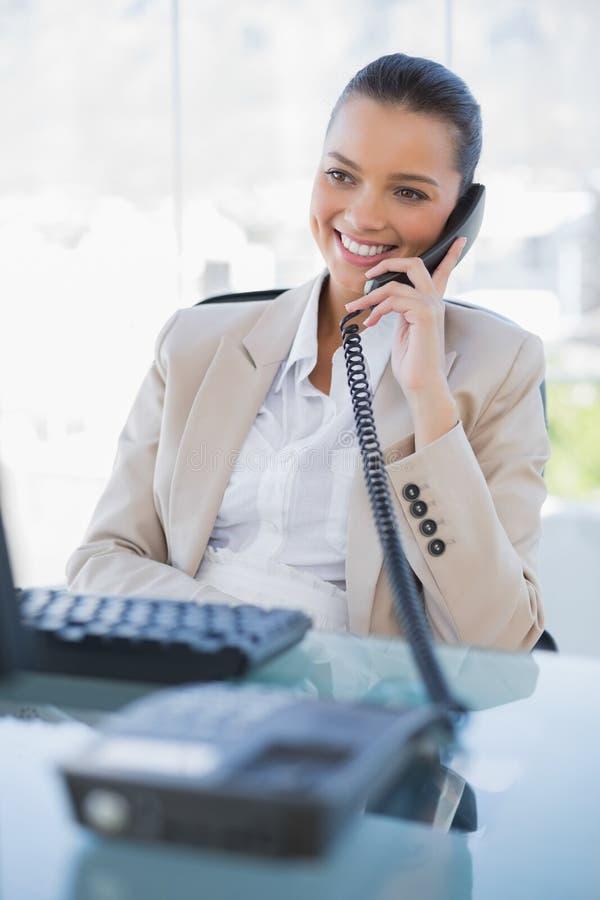 Glückliche herrliche Geschäftsfrau, die das Telefon beantwortet lizenzfreie stockfotografie