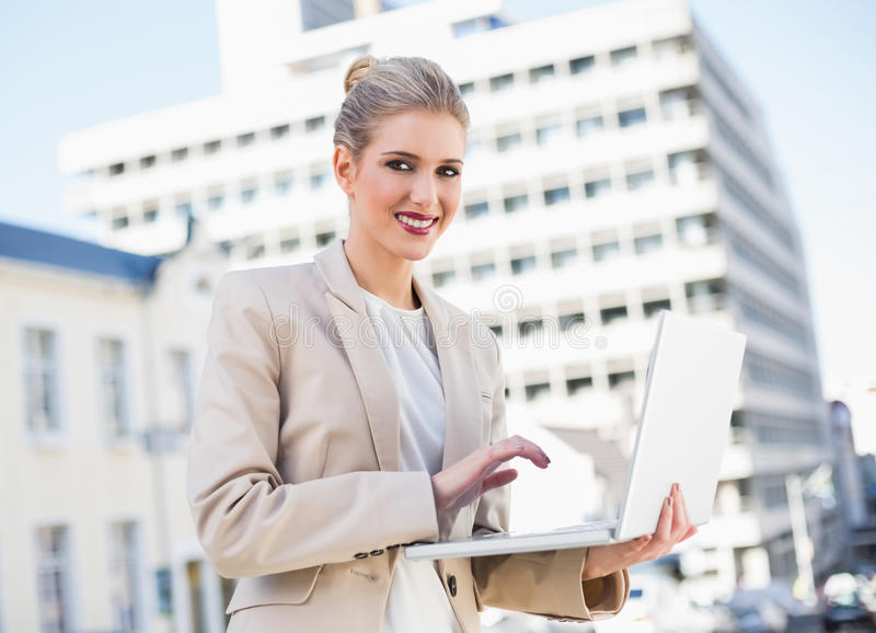 Glückliche herrliche Geschäftsfrau, die an Laptop arbeitet stockfotografie