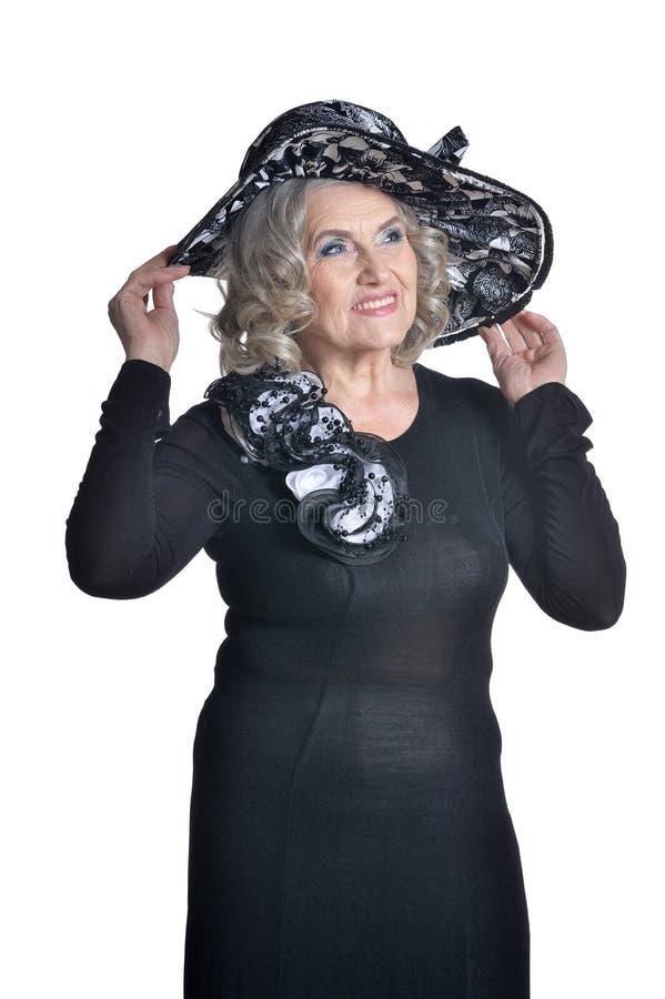 Glückliche herrliche reife Frau bei der Hutaufstellung lokalisiert auf weißem Hintergrund lizenzfreie stockfotografie