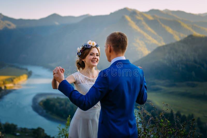 Glückliche Hochzeitspaare, die über der schönen Landschaft mit Bergen bleiben lizenzfreies stockfoto