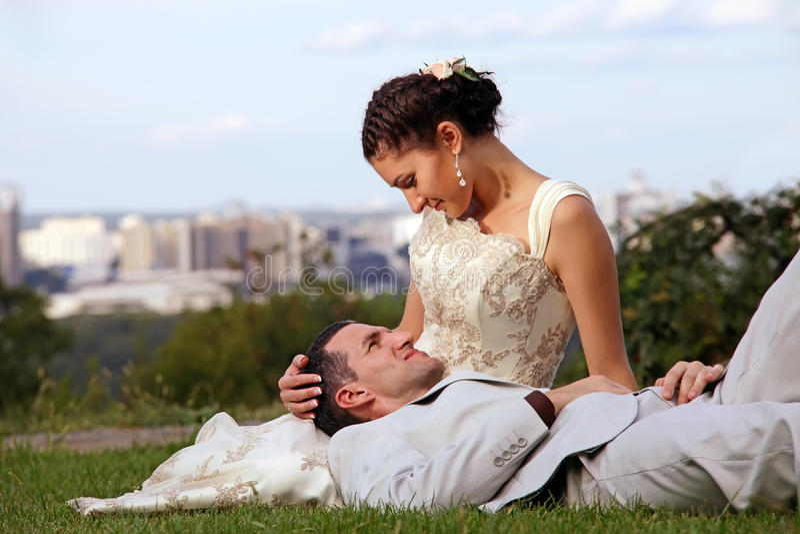 Glückliche Hochzeitspaare, die sich auf dem Gras hinlegen lizenzfreie stockfotos