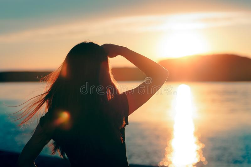 Glückliche hoffnungsvolle Frau, die den Sonnenuntergang durch das Meer betrachtet lizenzfreie stockbilder