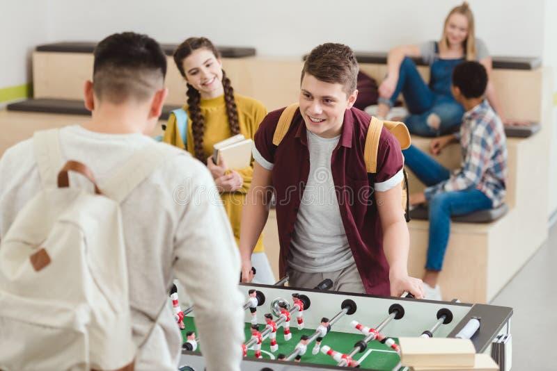 glückliche hohe Schüler, die Tischfußball spielen lizenzfreies stockbild