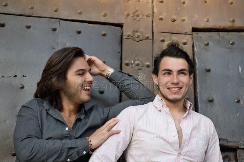 Glückliche homosexuelle Paare, die einen mittelalterlichen Platz in Katalonien besichtigen stockfotografie