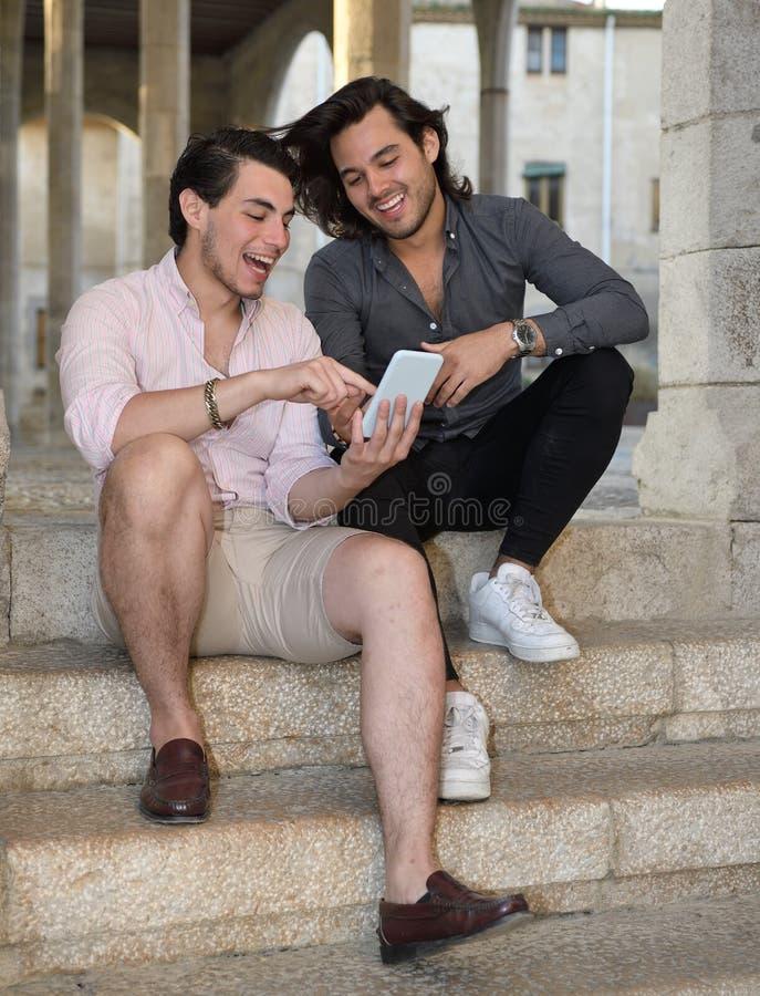 Glückliche homosexuelle Paare mit ihrem Handy stockfotografie