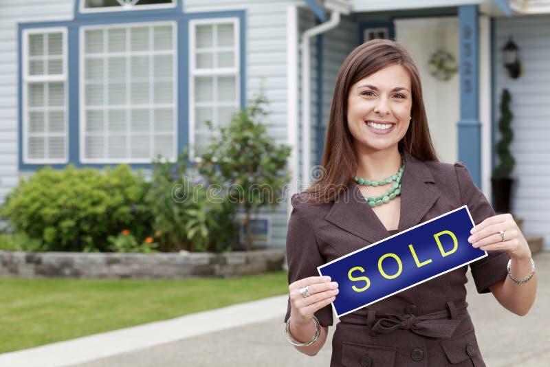 Glückliche Immobilienfrau hält ein Verkaufszeichen außerhalb eines Hauses lizenzfreies stockfoto