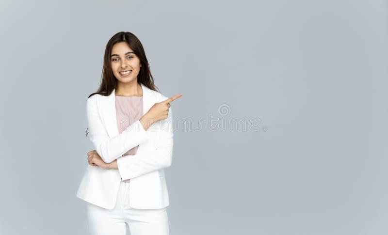 Glückliche indische junge Geschäftsfrau, welche die Kamera zeigt Finger auf copyspace betrachtet lizenzfreie stockfotos