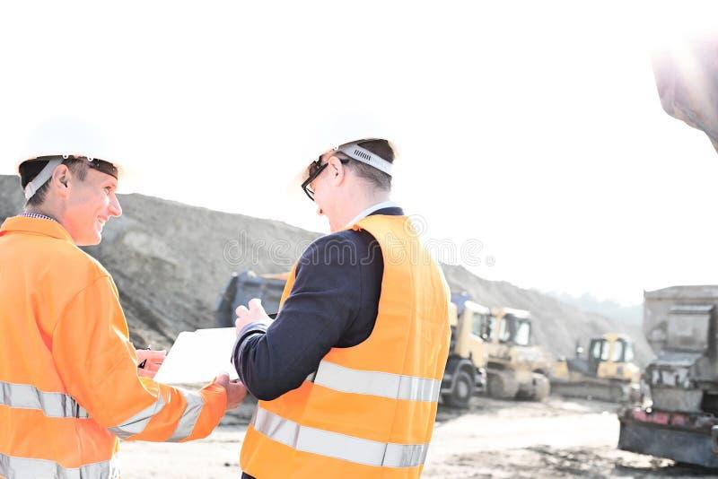 Glückliche Ingenieure, die über Klemmbrett an der Baustelle gegen klaren Himmel sich besprechen lizenzfreies stockbild