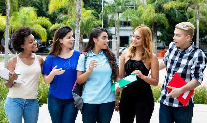 Glückliche internationale Studenten, die zur Universität gehen stockbild
