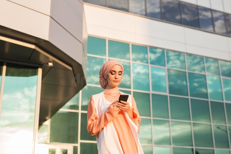 Glückliche islamische Frau, die intelligentes Telefon verwendet lizenzfreies stockbild