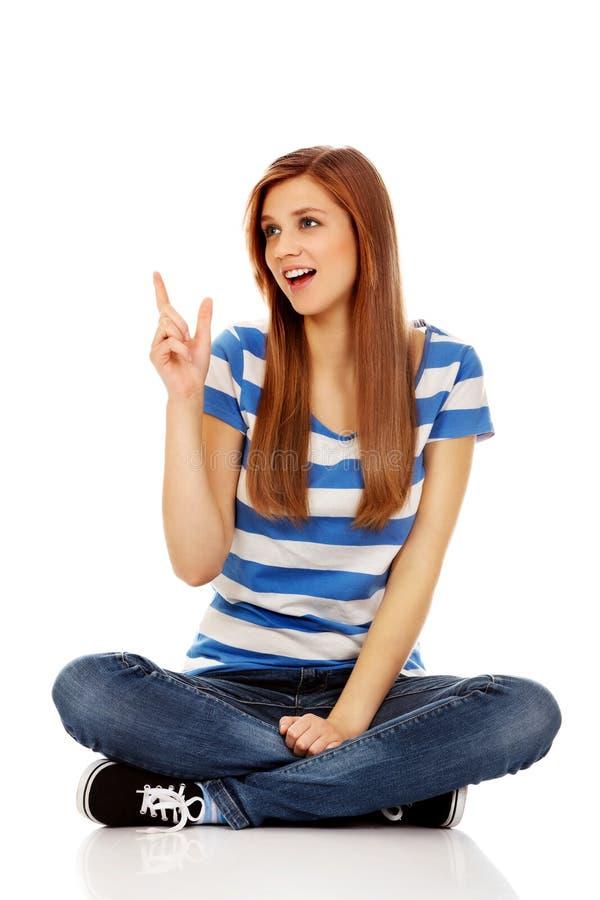 Glückliche Jugendfrau, die für etwas zeigt lizenzfreie stockfotos