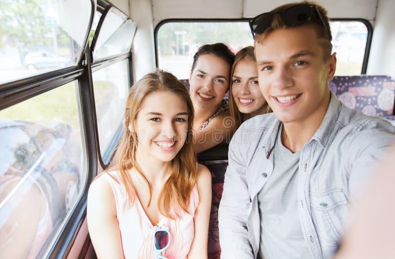 Glückliche Jugendfreunde, die mit dem Bus reisen lizenzfreie stockfotos