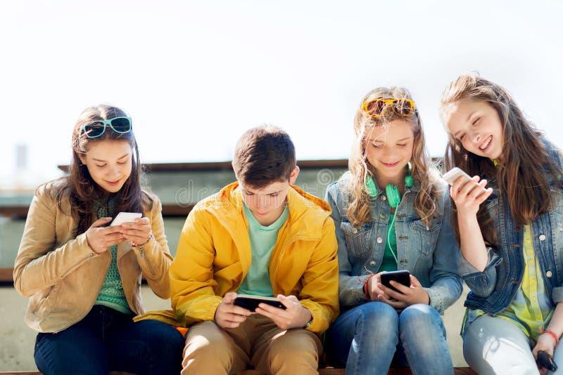Glückliche Jugendfreunde mit Smartphones draußen stockbilder