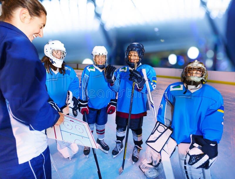 Glückliche Jugendhockeyspieler mit Trainer auf Eisbahn lizenzfreies stockbild