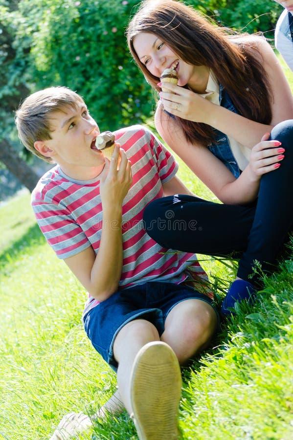 Glückliche jugendlich Paare, die Eiscreme am sonnigen Sommertag essen lizenzfreie stockfotos