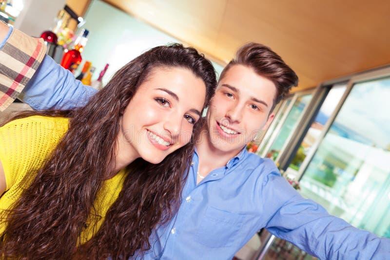 Glückliche Jugendlichpaare in der Stange lizenzfreie stockbilder