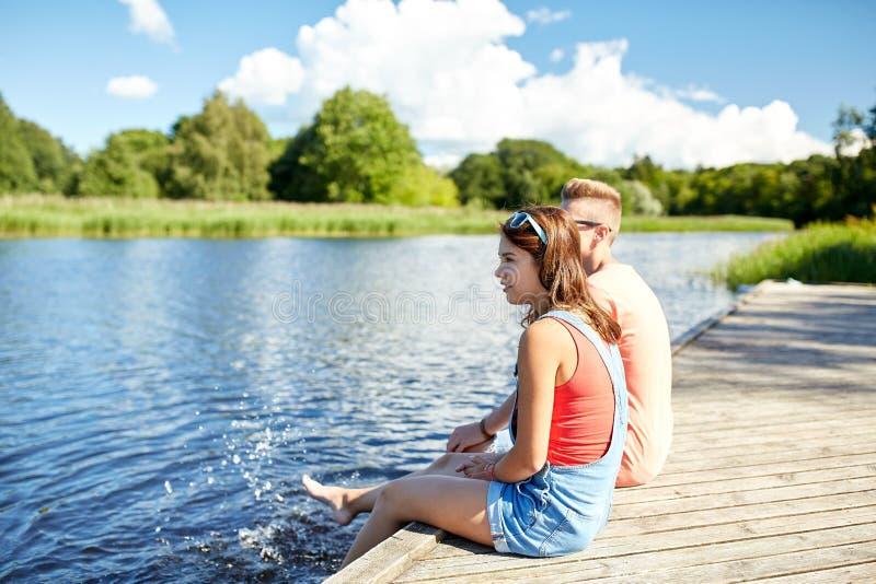 Glückliche Jugendpaare, die auf Flussliegeplatz sitzen stockbild