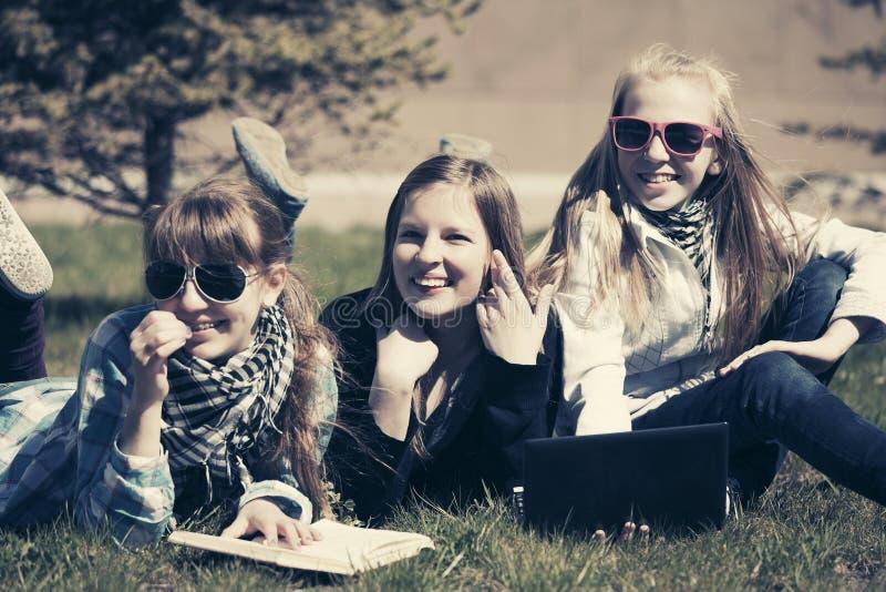 Glückliche Jugendschulmädchen, die auf Gras im Campus liegen lizenzfreies stockbild