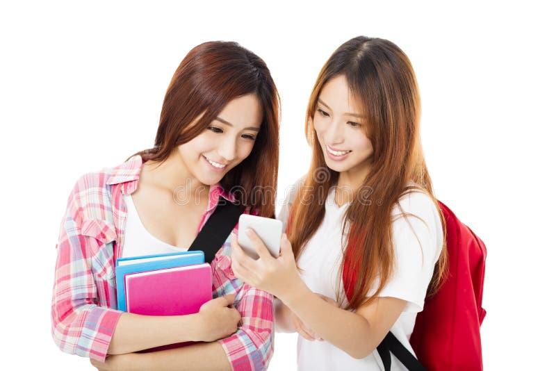 glückliche Jugendstudentenmädchen, die das intelligente Telefon aufpassen stockfotografie