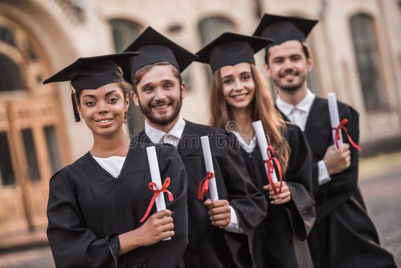 Glückliche junge Absolventen stockbild