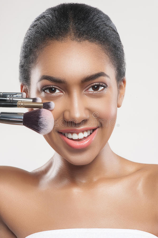 Glückliche junge afrikanische Frau mit kosmetischen Werkzeugen stockfotos