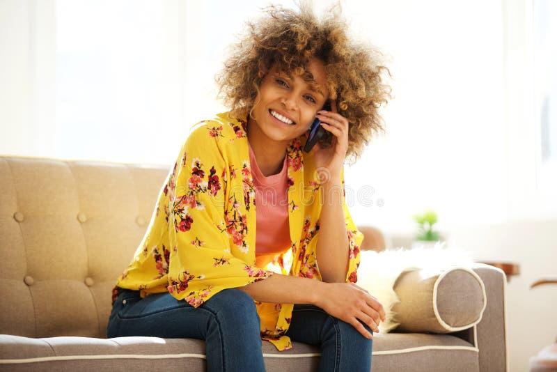 Glückliche junge Afroamerikanerfrau, die auf dem Sofa spricht am Handy sitzt lizenzfreies stockfoto