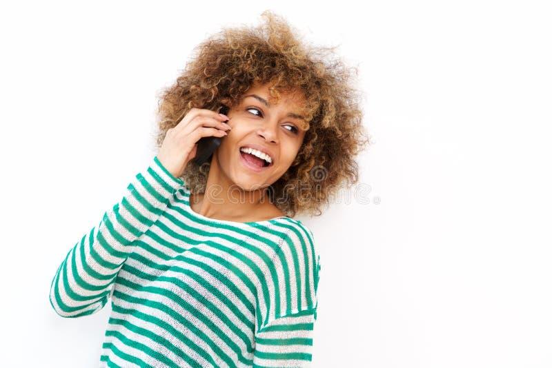 Glückliche junge Afroamerikanerfrau, die auf Mobiltelefon durch weißen Hintergrund spricht stockfotografie
