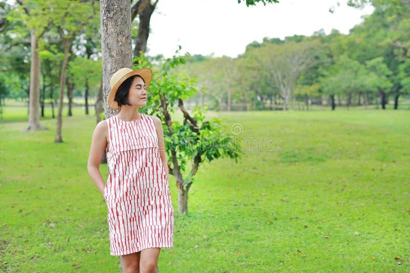 Glückliche junge Asiatin, die im Sommergarten sich entspannt Schlie?en Sie Augen stockfotografie