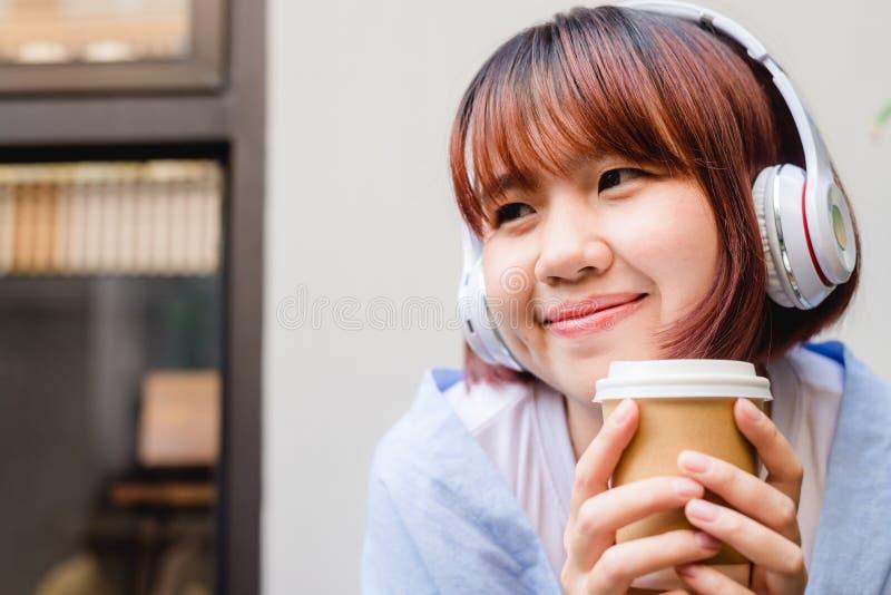 Glückliche junge Asiatin, die Musik in einer Kaffeestube hält einen Tasse Kaffee in ihrer Hand hört stockfotografie