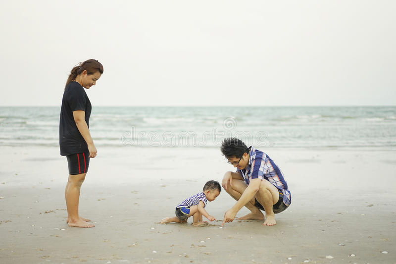 Glückliche junge asiatische Familie, die Spaß auf tropischen Strandferien O hat stockfotografie