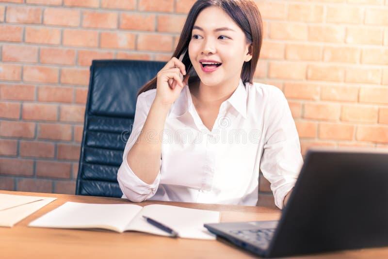 Glückliche junge asiatische Geschäftsfrau im weißen Hemd, das in ihr von arbeitet lizenzfreies stockfoto