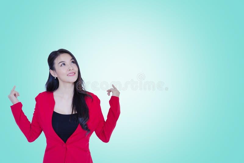Glückliche junge asiatische rote Klage der Geschäftsfrau, die auf cyan-blauer Farbe denkend steht lizenzfreie stockbilder