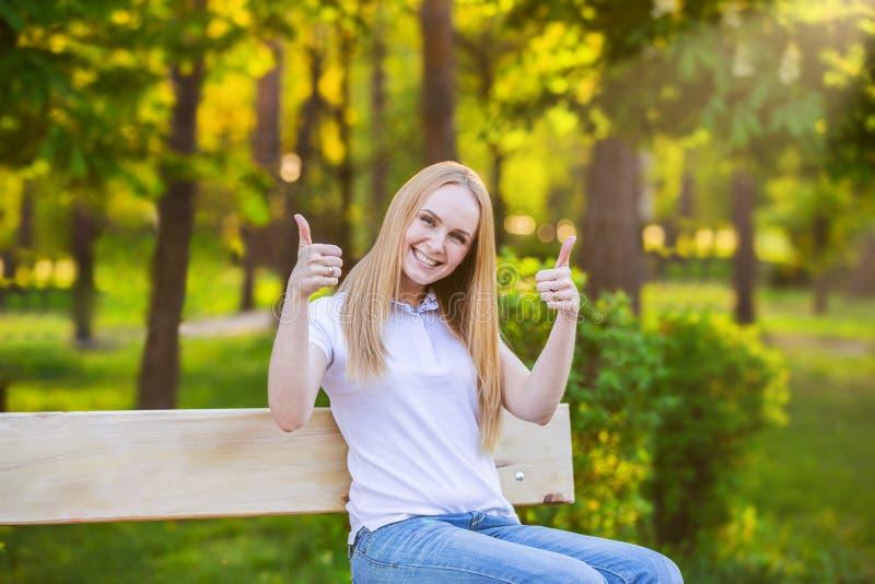 Glückliche junge blonde Frau, die Daumen oben auf einem grünen Sonnenhintergrund gibt stockbilder