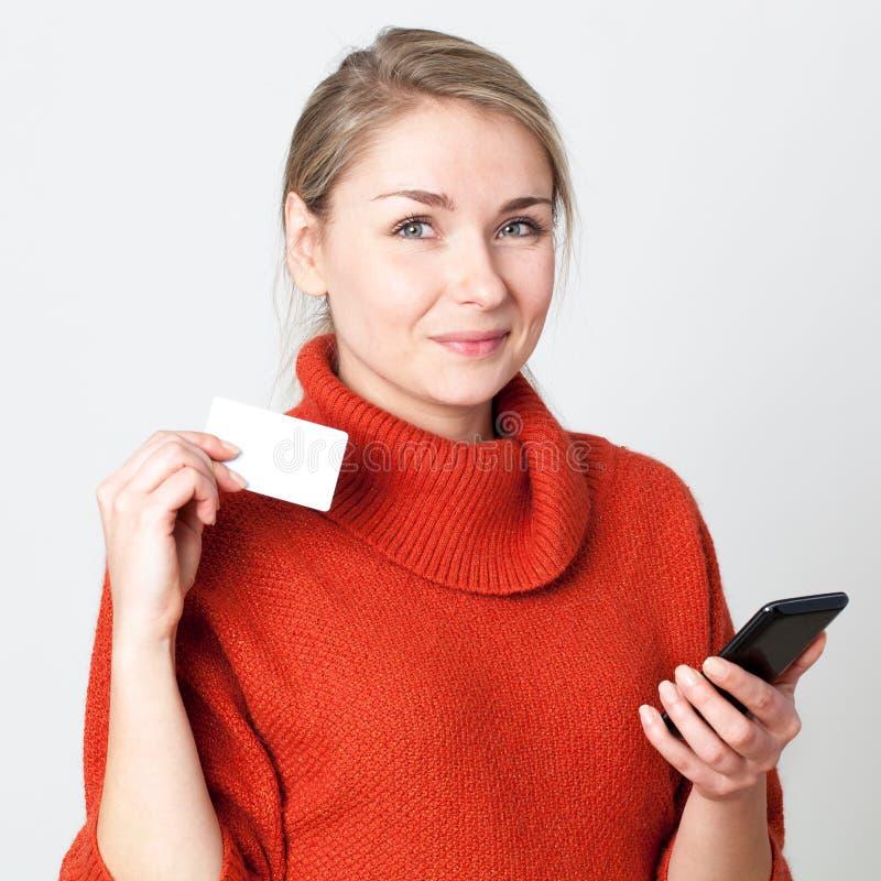 Glückliche junge blonde Frau, die am Handy mit Kreditkarte verbraucht lizenzfreie stockfotografie