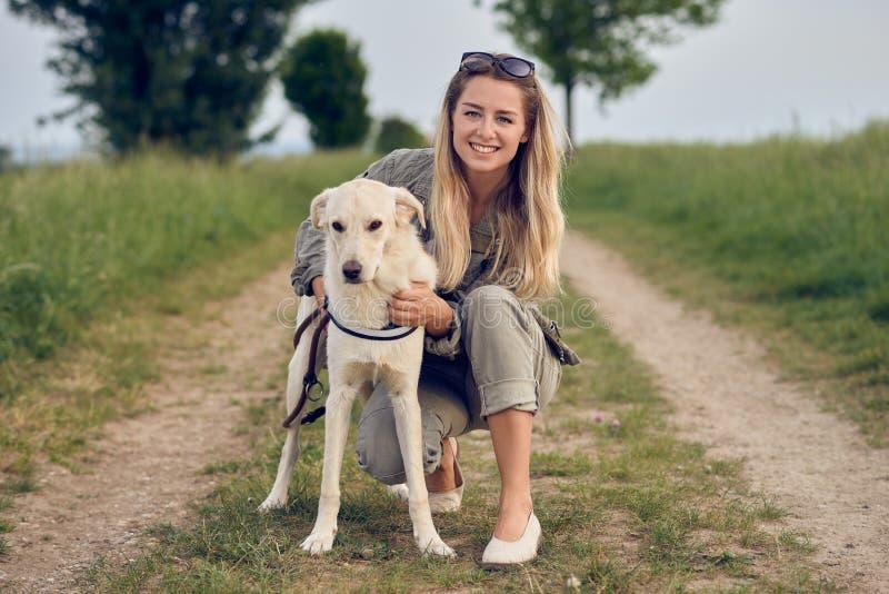 Glückliche junge blonde Frau mit ihrem Hund stockbilder