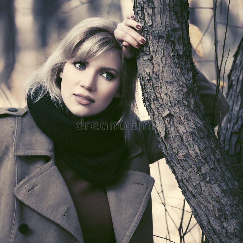 Glückliche junge blonde Modefrau, die in Herbstpark geht stockbild