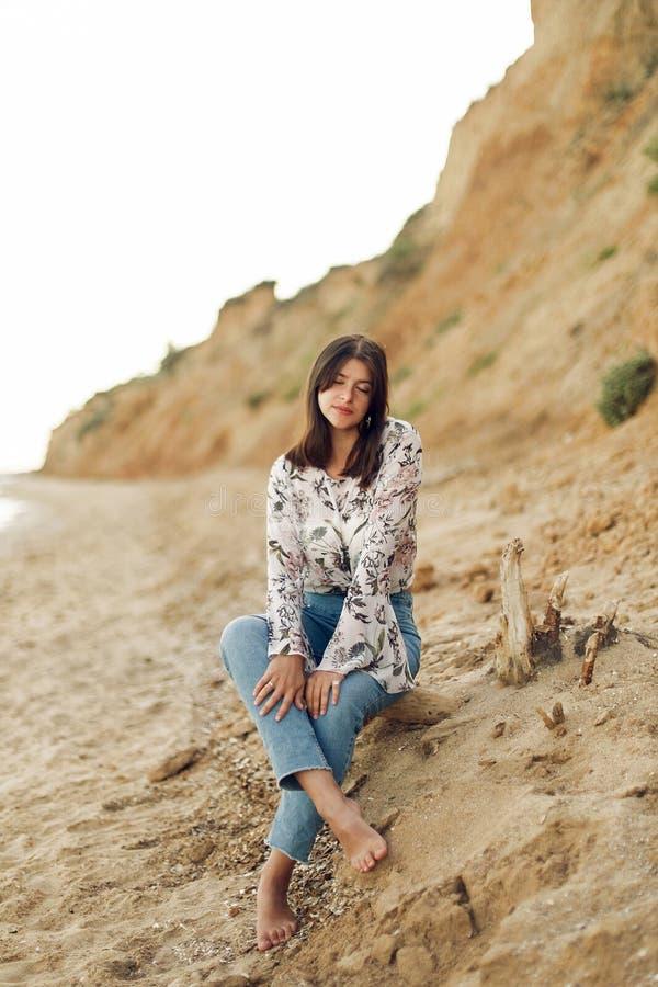 Glückliche junge boho Frau, die auf sonnigem Strand mit Felsen sitzt und sich entspannt Böhmisches sorgloses Mädchen des Hippies, stockfotos