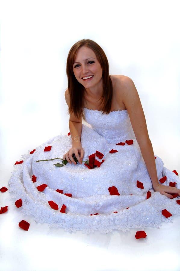 Glückliche junge Braut mit den rosafarbenen Blumenblättern stockfotografie