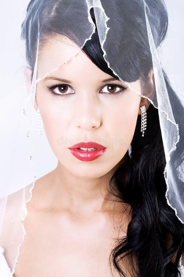 Glückliche junge Braut mit Schleier und den roten Lippen stockfoto