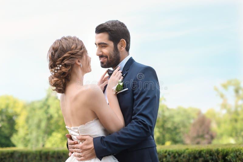 Glückliche junge Brautfestlegungsfliege ihres Bräutigams draußen lizenzfreie stockfotos