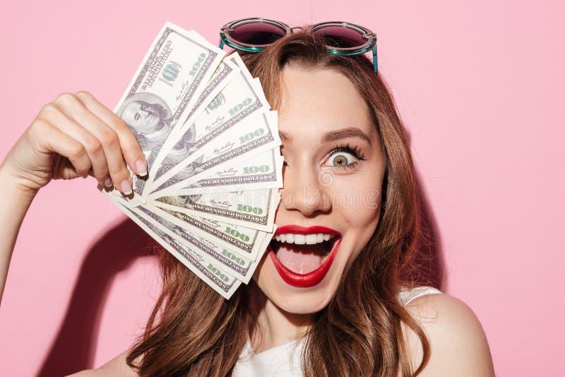 Glückliche junge Brunettedame, die Geld hält stockfotografie