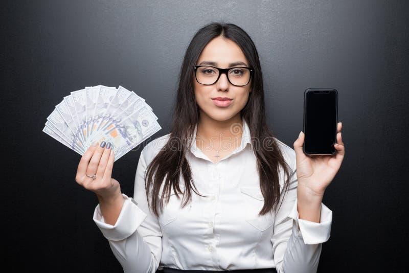 Glückliche junge Brunettefrau im weißen Hemd, das Smartphone mit leerem Bildschirm und Bargeld in den Händen lokalisiert auf schw stockfoto
