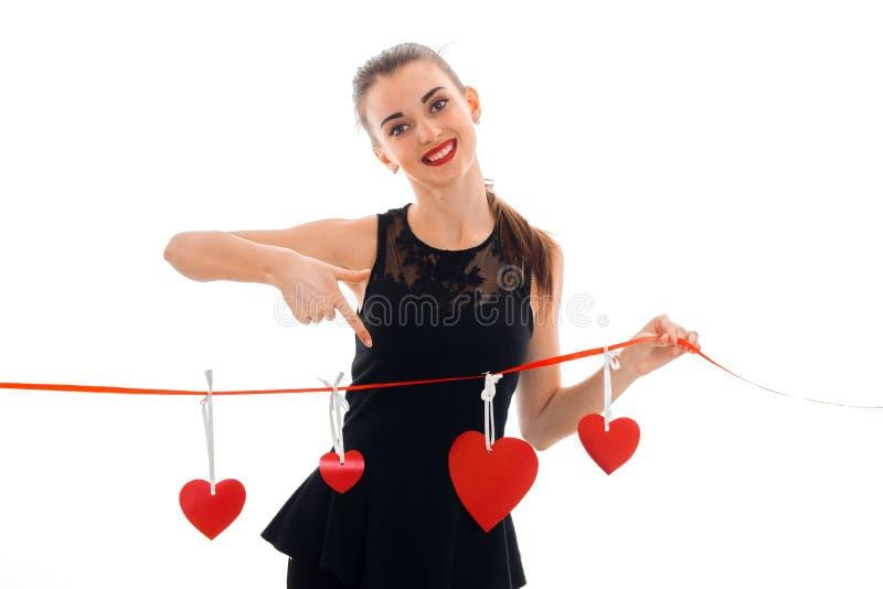 Glückliche junge Brunettefrau mit dem roten Herzen bei der Handaufstellung lokalisiert auf weißem Hintergrund Heilig-Valentinsgru lizenzfreies stockfoto