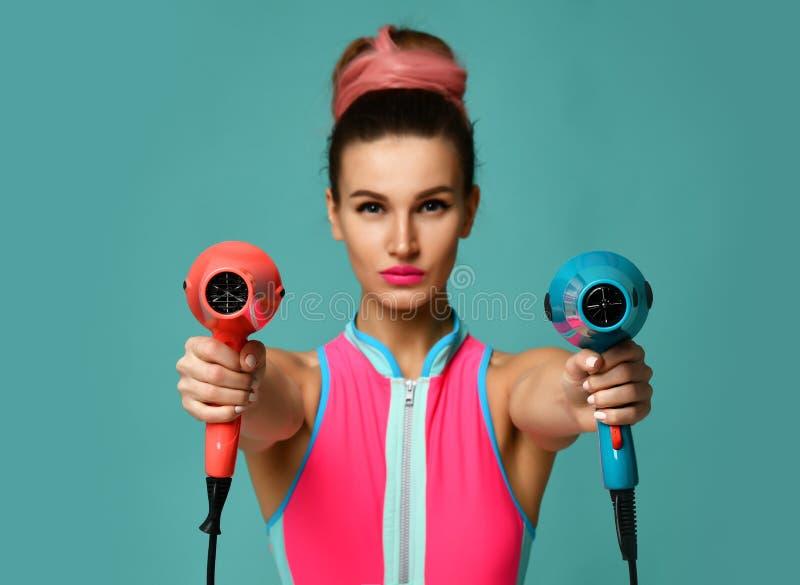 Glückliche junge Brunettefrau mit Haartrockner auf blauem tadellosem Hintergrund lizenzfreie stockbilder