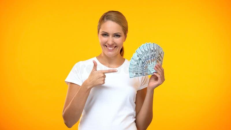 Glückliche junge Dame, die auf die Hand von Dollar-Banknoten zeigt, passives Einkommen, Investitionen stockfoto