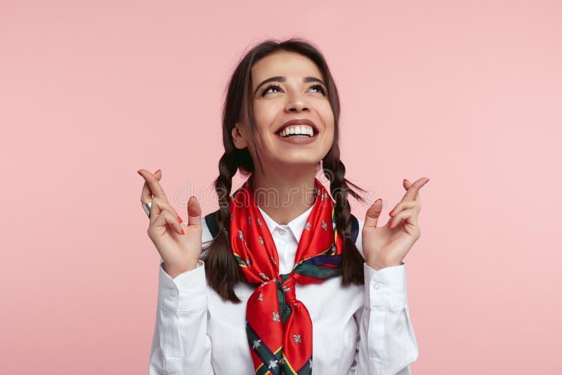 Glückliche junge Dame hat lustigen frohen Ausdruck, schaut oben und hält Finger gekreuzt für gutes Glück, angekleidet im weißen H stockfoto