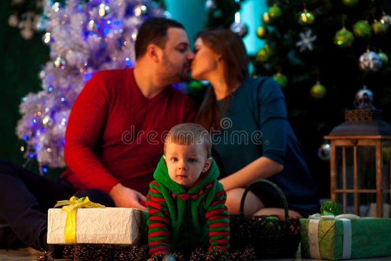 Glückliche junge Eltern küssen und ihr kleiner Sohn kriecht nahe Christus lizenzfreies stockfoto