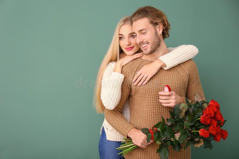 Glückliche junge engagierte Paare auf Farbhintergrund stockbilder